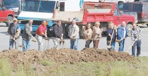 READY FOR CONSTRUCTION — Members of the Whitesburg City Council and Letcher Fiscal Court broke ground March 23 to start the construction of a pedestrian bridge in downtown Whitesburg. Pictured from left are Ked Sanders, a former county tourism commissioner, Magistrates Bob Lewis and Archie Banks, Letcher Judge/Executive Jim Ward, Whitesburg Mayor James Wiley Craft, Whitesburg City Council Members Shelia Shortt, Robin Watco, Frieda McFall and Jimmy Bates, and a local businessman Joel Beverly. The photograph below shows the location where the bridge will span the North fork of the Kentucky River.