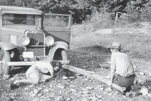 FSA photographer Marion Post Wolcott copes with car trouble in eastern Kentucky in 1940 — with the help of a local man and a fencepost as a jack.