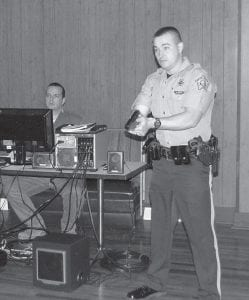 Letcher County Sheriff 's Deputy Jason Bates reacts to a recorded scenario being projected onto a large screen as part of a computerized training system. The simulations allow police officers to practice their decision-making skills when facing incidents such as a traffic stop, school shooting, bank robbery or a hostage situation.
