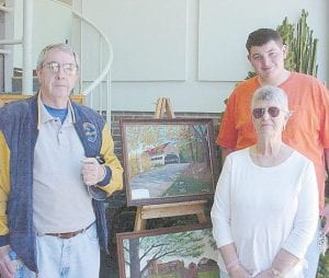 ON DISPLAY — Carl Banks (left) and Doris Adams and her grandson, Cody Dixon, enjoy the art exhibit at the Harry M. Caudill Library. Adams is one of the organizer and exhibitors.
