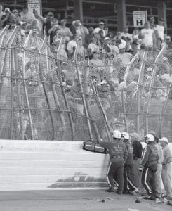 NASCAR officals looked at the damage to the fence after Carl Edwards's car hit it during a crash on the last lap of the Aaron's 499 Sprint Cup auto race at Talladega Speedway on Sunday. (AP Photo)