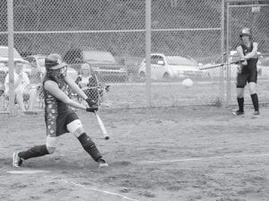 WHO HIT IT? The softball leaving the bat of Letcher County Central's Lisa Frazier appears in this photo like it could have been struck by the on-deck hitter. The ball landed for a double in the first inning of the Lady Cougars' game against Jenkins last week. (Photo by Chris Anderson)