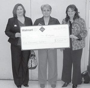 Employees of Whitesburg Wal-Mart recently presented Kimberly Eldridge, development officer of Hospice of the Bluegrass Mountain Community, and Monica Couch, director of Hospice of the Bluegrass- Mountain Community, with $5,000 to help build a free-standing inpatient facility in Hazard which will serve residents of Letcher County. Pictured in tbetween Eldridge and Couch is Earline Delph, store manager of the Whitesburg Wal-Mart.