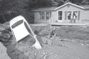 Carl Mills of Red Jacket, W.Va., sat on his front porch behind his two automobiles that were washed into a small creek flowing in front of his house when flash flooding hit his community on May 8. (AP Photo)