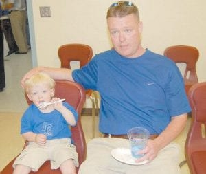 Robert Hammonds, new head basketball coach at Letcher County Central High School, sat beside his 22-month-old son Paxton while he ate cake at a press conference and community greeting held in Whitesburg May 19.
