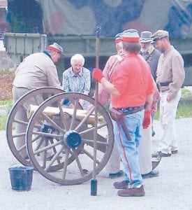 MEMORIAL DAY — Lizzie Mae Wright (center) was one of three people selected to fire the antique cannon at the Letcher County Veterans Museum in Whitesburg on Memorial Day. The other two were a soldier who was home on leave and a member of the Seventh Sons Motorcycle Club.
