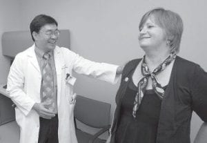 Dr. Patrick Hwu, left, talked with his cancer patient Hilde Stapleton during an examination last week at The University of Texas MD Anderson Cancer Center in Houston. Stapleton has been receiving an experimental treatment for melanoma. (AP Photo)
