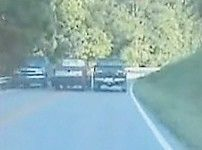 This image captured by a video camera mounted on a Letcher County Sheriff 's Department cruiser shows a pickup allegedly being driven by Ethan Kisor as it drves between two other pickups on a narrow section of KY 7.