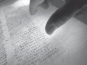 This undated picture made available by the British Library shows a reader examining a page from the earliest surviving Christian Bible. The British Library says the surviving pages of the world's oldest Bible have been reunited — digitally. The library says the early Christian work known as the Codex Sinaiticus had been housed in four separate locations across the world for more than 150 years. It became available for perusal on the Web so scholars and others can get a closer look. (AP Photo/The British Library)