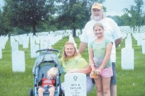 Herbie Adams, who died in a wreck on July 14 in Pound, Va., is pictured with his wife and two children at the gravesite of former Letcher County Sheriff Ben Buster Taylor during a recent visit to Arlington National Cemetery. Adams told his wife, Gina Vonda Adams, that he had always wanted to visit the cemetery, so they did on June 28. Pictured from left are two-year-old Zane Ellis Adams, Gina Vonda Adams, 10-year-old Tayler Lee Adams and Herbie Adams.