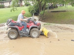 Above, Thornton resident Sammy Warf used a blade and an all-terrain vehicle to help clear mud and other debris from KY 1862 after a culvert that is turned upstream became stopped up during a heavy downpour on Sunday afternoon.