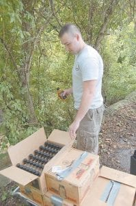 Letcher County Sheriff 's Deputy Jason Bates emptied out old containers of confiscated alcohol near the banks of the North Fork of the Kentucky River in downtown Whitesburg last week. (Eagle photo)