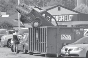 A woman shopped last week for a car at Springfield Auto Mart in Springfield, Vt., a dealer for Buick, Pontiac and GMC. Above her is a car that was dumped in a Dumpster as a visual promotion for the government cash-for-clunkers program. (AP Photo/Rutland Herald)