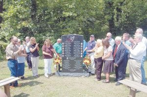 AT THE UNVEILING — Stella Morris, fourth from left, and UMW President Cecil Roberts, joined in the applause given by family members and others after a memorial to coal miners killed on the job or by black lung was unveiled on August 14. Morris, whose husband was killed in a mining accident in 2005, raised the $10,000 needed to pay for the monument, mostly through bake sales and roadblocks. (Photo by Roy Silver)