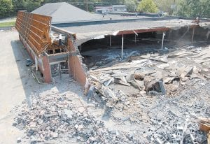 Paul Hall, 47, of Neon, was working under a section of the roof of the old A&P building that was still intact when the roof began collapsing on August 18. Hall was taken to the Whitesburg Appalachian Regional Hospital by ambulance and was treated and released. In the photograph above, Hall, pictured wearing a yellow hard hat, was sorting through debris on August 13. (Photo by Sally Barto)