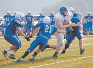GETTING READY — Letcher County Central High School's new quarterback, sophomore Logan Johnson, broke a pair of tackles on a rushing attempt during the Cougars' scrimmage against visiting Breathitt County on August 13. (Photo by Chris Anderson)