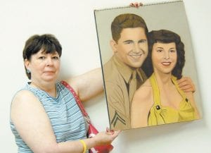 Patricia Holbrook holds a painting of a young couple she believes to be from the 1940s or 1950s. (Eagle photo)