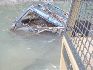 Volunteers used a piece of heavy equipment to remove this Ford Explorer from the North Fork of the Kentucky River.