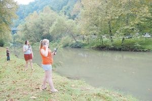 MULTI-TASKING ON LABOR DAY — Paige Caudill, 12, of Whitesburg talked on a cellular phone while she competed in a fishing tournament held at the City of Whitesburg's Labor Day Celebration at River Park on Sept. 7. Paige is the daughter of Stephanie McFall and Jim Caudill. Michaela Miracle, 13, of Mayking is pictured fishing in the background. Michaela is the daughter of Robert and Sheila Miracle.