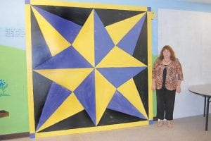 Jenay Hall, a librarian at the Harry M. Caudill Library in Whitesburg, recently painted an eight-footby eight-foot quilt barn square to be mounted on the Lillian Webb Memorial Library in Neon. Hall said the star pattern was painted purple and gold to represent traditional Neon colors. Legina Adams, bookmobile librarian, and Jenay Hall's 17-year-old daughter, Tazsha Hall helped Jenay Hall paint the large square. Hall is now working on a large barn quilt square to be mounted to the back of the Whitesburg library. The multicolored design