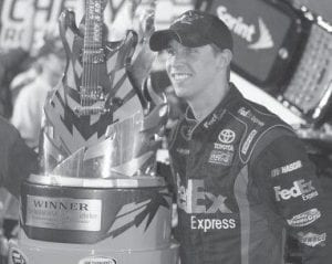 Denny Hamlin posed with the trophy after winning the NASCAR Sprint Cup Series' Chevy Rock & Roll 400 auto race at Richmond International Raceway in Richmond, Va. (AP Photo)