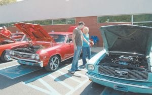 COOL CARS — Eric Potter, of Hemphill, pointed out a detail on a car to Brittany Maxie, of Whitesburg, at the Heritage 2K9 c ar and truck show held ne ar Mountain Comprehensive Health Corporation in West Whitesburg on Sept. 12. Potter said he has attended the past four shows, while this was Maxie's first time. Potter said he attends each year
