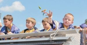 Above, Fleming-Neon Elementary School football players rode atop a fire truck and tossed candy to parade-goers during the Neon Area Days Parade. Pictured at right is Samara Adams, who cruised through the parade on the top of a pickup truck.