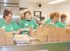 KEEPING PATIENTS AND WORKERS FED — Volunteers Mary Lumpkins, Tori Short, Elsa McCoy and Amanda Mullins packed meals during the Remote Area Medical Volunteer Corps (RAM) expedition held at Jenkins High School on Sept. 26.