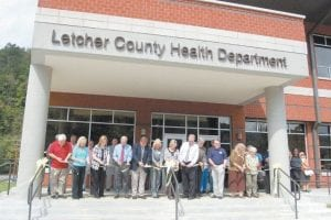NEW BUILDING DEDICATED — A ribbon-cutting ceremony for the new Letcher County Health Department in Whitesburg was held Sept. 23. Pictured from left are Letcher County Health Department Board Member and District 5 Magistrate Wayne Fleming, Health Department Director Lana Polly- Mullins, Board Member Dr. Katherine Gish, Whitesburg Mayor James Wiley Craft, Board Member Letcher Judge/Executive Jim Ward, State Rep. Leslie Combs, Board Member Eleanor Caudill, Board Member Dr. Bill Collins, Bill Richardson, architect of the project, Board Member Dr. David Narramore, District Director of the Kentucky River Health Department Karen Cooper and Mabel Jo 'Ma' Buttrey, who is thought to be the first clerk of the health department. Buttrey worked as a clerk from 1940- 43.