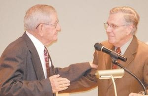 Former Letcher County Sheriff Maynard Hogg is greeted by Southeast Kentucky Community and Technical College President W. Bruce Ayers during a ceremony naming the college's Allied Health building after Hogg, who became active in the coal business after his term as sheriff ended in the late 1960s, and his family.