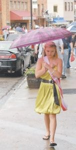 Miss Teen Mountain Heritage Courtney Fields tried to keep herself sheltered from the rain as she walked up Main Street after riding on the top of a car during the parade.