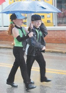 Makenna Johnson and Bailey Kincer walked through the rainy parade after performing a routine as part of the Silver Spinners baton twirling team.