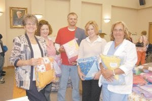 Participants in the Letcher County Drug Court made 40 quilts to be distributed to babies born dependant on drugs. The blankets were given to Leanna Ison, chief nursing officer at Whitesburg Appalachian Regional Hospital, and Diane Watts, nurse manager of obstetrics and pediatric department at Whitesburg ARH, at a drug court graduation held in the Letcher Circuit Courtroom on Oct. 9. Pictured from left are Ison, Letcher County Drug Court participants Andrea Cornett, Curtis Branham and Tabitha Madden and Watts.
