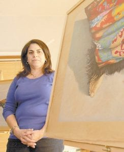 Breast cancer survivor and artist Helen Rowles poses with work from her