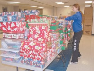 Sorting out gifts Courtney Winskey, 17, gathered shoeboxes filled with gifts at the First Baptist Church in Whitesburg on Nov. 17. Winskey spent all evening filling shoeboxes with toiletries, candy, toys and school supplies to be delivered to needy children worldwide. This is the seventh year the Whitesburg church has participated in Operation Christmas Child.