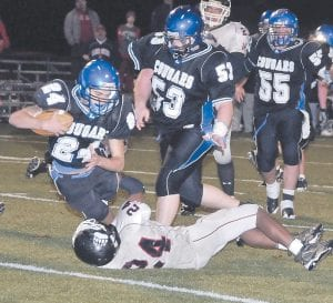 GAME-TYING PLAY — A long scoring drought was ended by Letcher Central's Greg Collins on this rushing attempt. Collins was wrapped up, but not before breaking the goal-line plane for a Cougar touchdown that tied the game at 13. LCC scored the point-after and escaped with a 14-13 win over Harlan County. (Photo by Chris Anderson)