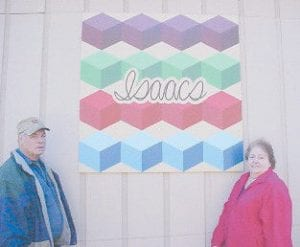 QUILT SQUARE — Creda and Clester Isaacs show off a new quilt square installed on the garage at their home at Deane as a part of the Letcher County Quilt Heritage Project. The pattern is a personalized variation of the tumbling block quilt pattern which uses three shades of a color to give the cubes a three-dimensional appearance. The square was painted on one-half inch plywood which measure four feet by four feet. The project is part of the eight-county Elk County Corridor project to honor and preserve the area's heritage and promote tourism. Clester Isaacs is retired from Golden Oak Coal Company and Creda Isaacs worked at Parkway Pharmacy in Whitesburg prior to retirement. She remains active as president of the Letcher County Historical and Genealogical Society. For more information about the quilt heritage project, call Sharman Chapman-Crane at 633-5065.