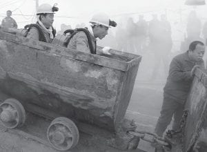 A coal miner helped rescuers ride a railway trolley as they headed into the site of a gas explosion at the Xinxing mine in Hegang, Heilongjiang province, China, on Sunday. The huge gas explosion in the northern Chinese mine is the deadliest blast to hit the beleaguered industry in nearly two years. (AP Photo)