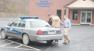 Murder suspect Christopher P. Smith used his coat to cover his head from a photographer Tuesday as he was being helped into the back of a Kentucky State Police cruiser for transport to the Harlan County Jail. Smith surrendered earlier in the morning to Letcher County Sheriff Danny Webb. (Eagle photo)