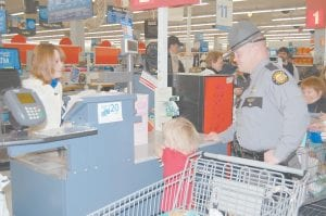 SHOPPING WITH A COP — Kentucky State Police Trooper Adam Hall looked on as cashier Kayla Taylor placed a little girl's new toys into bags during the Shop with a Cop event at the Whitesburg Walmart.