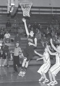 COUGARS ATTACK CAVS — Letcher County Central High School freshman Dewey Baker laid in two points during the Cougars' 96-10 rout of a young Jenkins team last week. Freshmen Jacob Campbell and junior Matthew Edwards defended the play. (Photo by Chris Anderson)