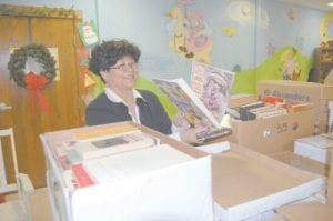 Lena Tidal, director of the Letcher County Public Library District, smiled as she pulled children's books out of a box on Dec. 10 in the basement of the Harry M. Caudill Memorial Library in Whitesburg. Jim Davis, a Bullitt County man who is battling terminal cancer, decided to collect 10,000 books from friends, families, churches and other organizations to be distributed to libraries in eastern Kentucky.