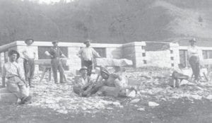 """STONE MASONS — The foundation for the new high school in Whitesburg was laid prior to 1914. The United States needed skilled workers, so they sent notices out to other countries. Italy had a lot of men without work, so some of them decided to come to the U.S. and some of them settled in Whitesburg. They mined """"blue stone"""" out of a quarry next to the school hill and cut and laid it by hand to form the foundation on which the school was built. The gentleman lying down in the center of the picture is Frank Majority Sr. and seated next to him is his brother, Vincent Mongiardo. Vincent Mongiardo kept the family's original spelling and is the grandfather of Lt. Gov. Dr. Daniel Mongiardo of Hazard. Frank Majority Jr. of Whitesburg used his father's shortened spelling of his name."""