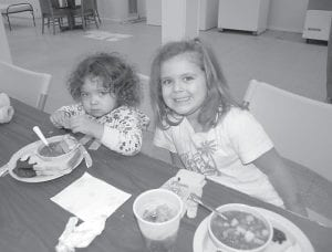 SHELTERED FROM THE COLD — Two-year-old Makayla Madden and her sister, five-year-old Jessica Madden, ate soup at the Boonefork Senior Citizens Center at Neon on Dec. 20. The girls are the daughters of Kristen Madden and Joseph Mclemore of Dunham. Five senior citizens centers in the county are being used as shelters for those who are still without electricity. (Photo by Sally Barto)