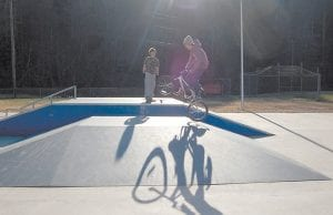 FUN IN THE SUN — Jeff Caudill, 14, performed a trick on his bike Tuesday at the Letcher County Skate Park in West Whitesburg while his twin brother, Chris, watched as he stood on a skateboard. (Photo by Sally Barto)