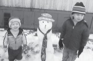 WINTER WONDERLAND — Aaron Sexton, 1, at left, and his brother, Joseph, 4, enjoy playing in the snow when the snowstorm arrived just a week before Christmas. The two boys helped their father build this snowman. They are the children of Mark and Katherine Sexton of Whitesburg.