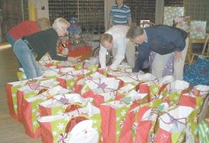 Tree of Hope organizers Glenda Brown and Glenda Banks, Cumberland River Coal Company employee Seth Collins, and District Two Magistrate Archie Banks sorted through gifts last month. Employees of Cumberland River donated $1,800 to buy Christmas presents for 33 children here.