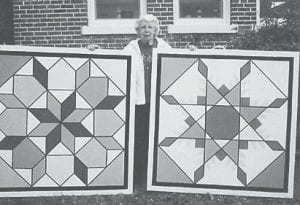 QUILT SQUARES — Judith Vermillion is pictured with the quilt squares she painted for the Ermine Senior Citizens Center. The quilt pattern at left is Star of the East and that at right is Feathered Star.