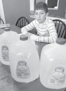 Jay Miller, 12, sits behind three jugs of bottled water on the kitchen table. The Miller family buys bottled water for Jay, who has allergic reactions to sulfates, when the level of that pollutant rises in their tap water. Last year, Miller mysteriously developed hives that itched and bothered him for two weeks. Then his mother read about spiking levels of pollution in the nearby Monongahela River, the source of their tap water. (AP Photo)
