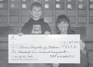 DONATION — Six-year-old Aaron Adams presents Jenna Taylor, associate director of development at Shriners Hospital in Lexington, with a check for $1,322.58.